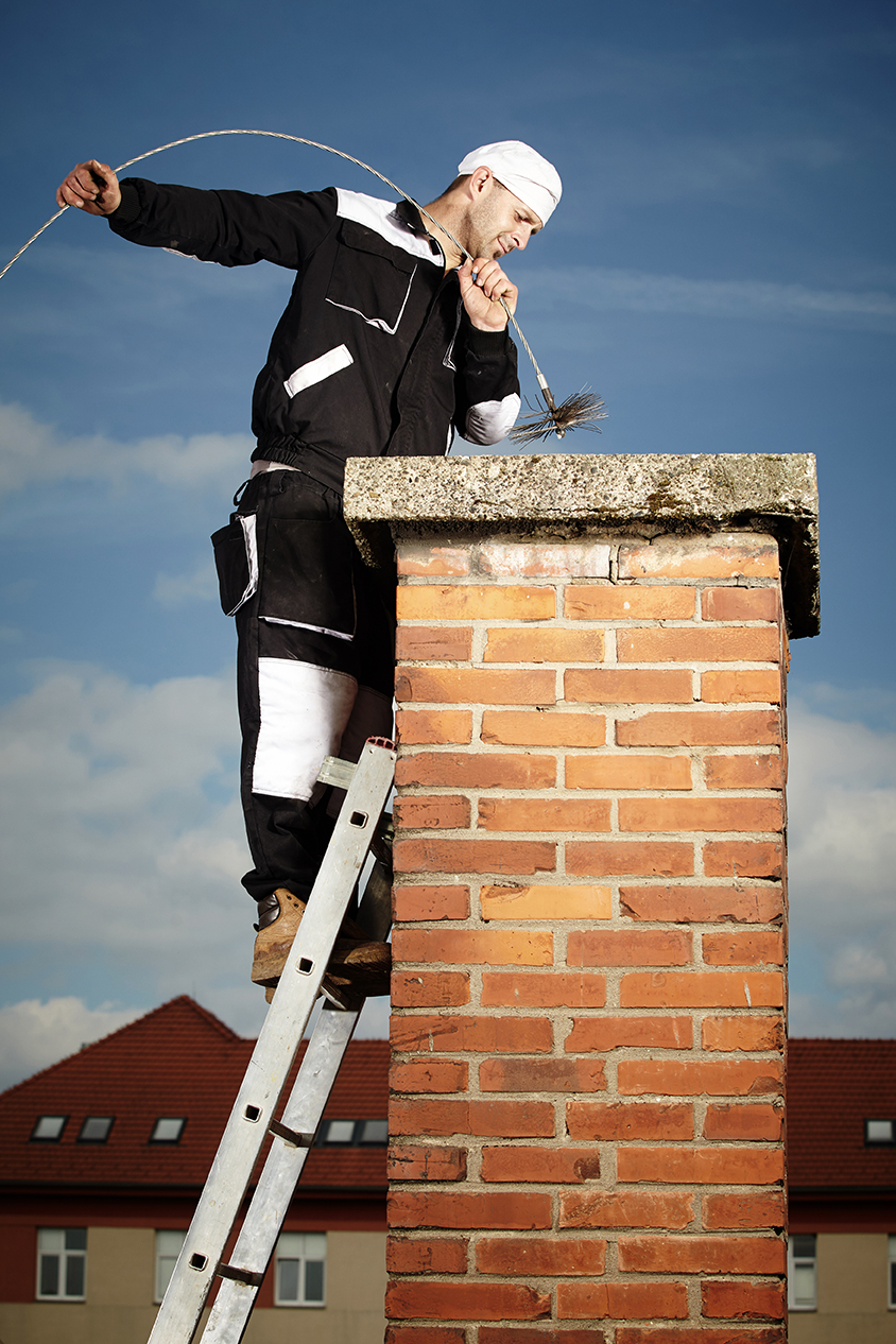Chimney sweep man in work uniform cleaning brick style chimney on building roof