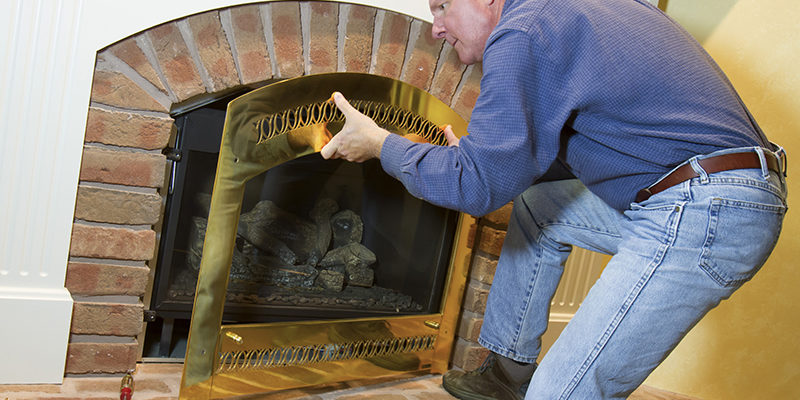 Man doing installation, repair, or seasonal maintenance on a built-in gas fireplace